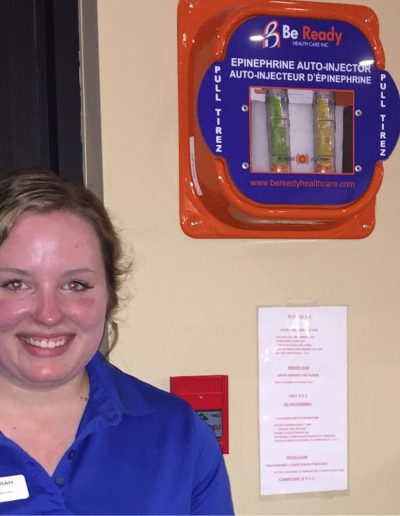 Smitty's employee with emergency kit on wall behind her